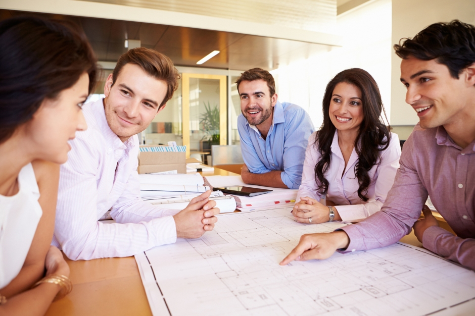 Group Of Architects Discussing Plans In Modern Office